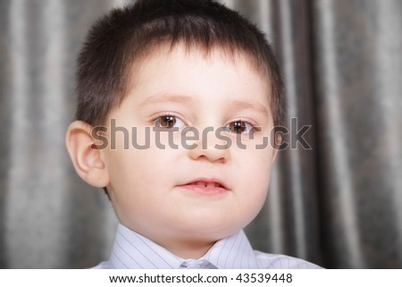 Little cute brunette boy in white shirt closeup photo