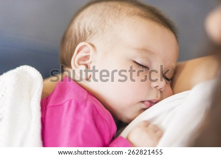Little Cute Caucasian Infant Sleeping on Mothers Hands Indoors. Horizontal Image Composition - stock photo