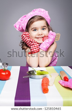 little cute chef holding wooden spoon with different pair of gloves looking at camera and smiling on gray background - stock photo