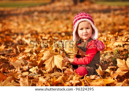 Little cute child girl in autumn leaves