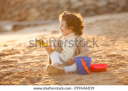 Little cute child girl sitting on sand and playing with toys, outdoor - stock photo