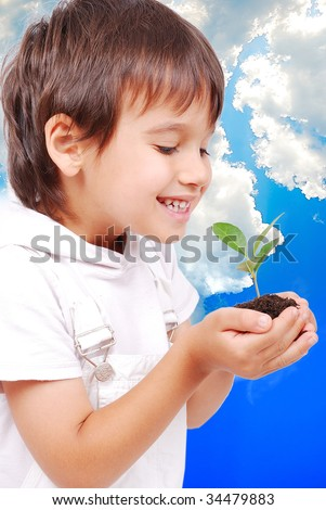 Little cute child holding green plant in hands - stock photo
