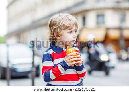 Little cute child on a street of city eating fresh croissant, on warm day. - stock photo