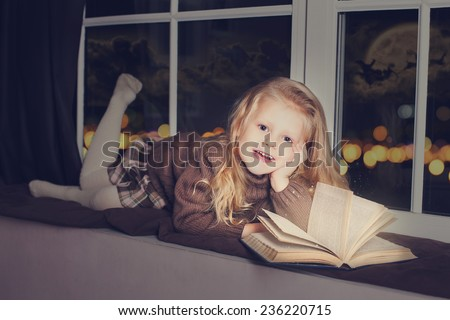 Little cute child reading a book and dreaming of Santa at home, indoors - stock photo
