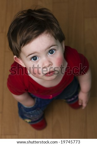 Little cute child with beautiful large eyes looking up at the camera. Hand in pocket. - stock photo