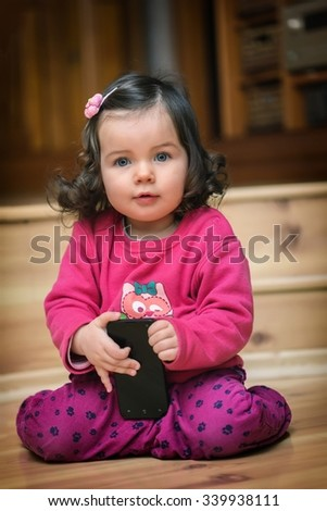 Little cute curious baby girl with dark curly hair holding mobile phone - stock photo