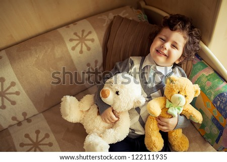 little cute curly  boy laying at couch with teddy bear,top view - stock photo