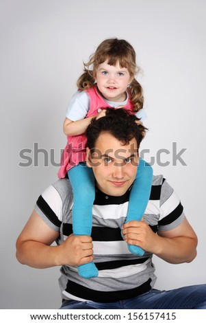 Little cute daughter sits on shoulders of his father on grey background.