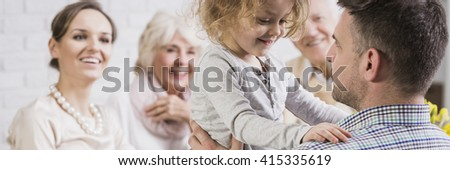 Little cute daughter standing n father's knees. Young mother and grandparents looking at her with smile and love