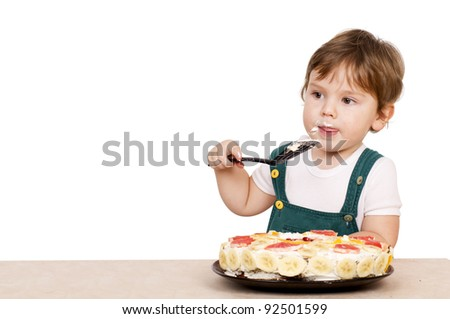 Little cute eating a cake. Isolated on white. - stock photo