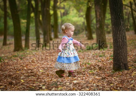 Little cute elegant beautiful girl walks in autumn park