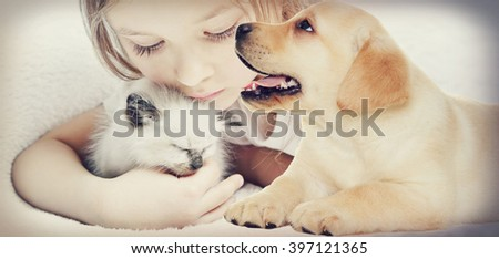 little cute girl affectionately hugging  kitten and puppy - stock photo