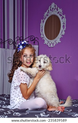 Little cute girl and dog in home interior - stock photo