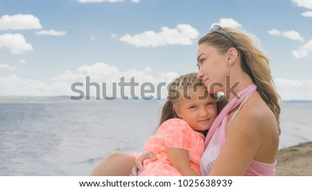 Little cute girl baby and young mother at beach. Mom sits on the shore, and her daughter is coming from behind. The kid hugs and kisses her mother. Mother and her child.