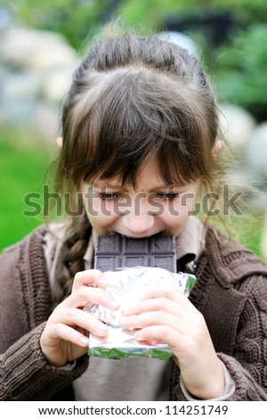 Little cute girl biting big tablet of chocolate, focus on girl's face - stock photo