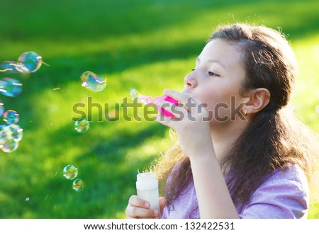 Little cute girl blowing soap bubbles outdoors. Summer