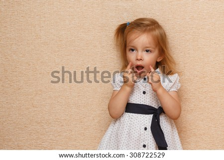 Little cute girl building faces. Positive emotions. The concept of carefree childhood. - stock photo