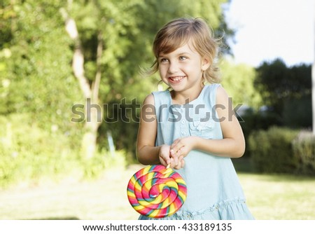 Little cute girl eating a big candy outdoor - stock photo