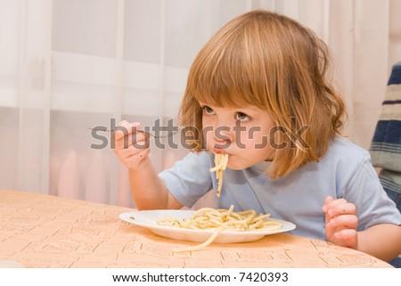 little cute girl eating spaghetti with pesto sauce - stock photo