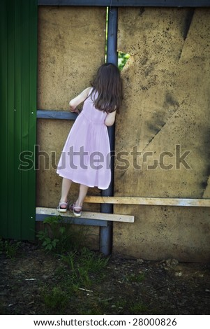 little cute girl five years old looking through hole in wall - stock photo