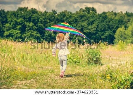little cute girl flying a kite in a meadow on a sunny day, back view - stock photo