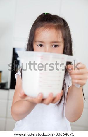 Little cute girl holding milk in a measuring mug - stock photo