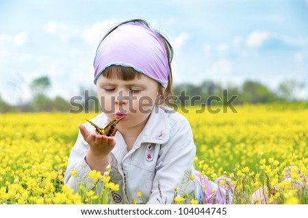 Little cute girl in a field of beautiful yellow flowers holding a butterfly on the palms and blowing on it. - stock photo