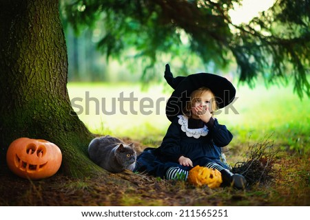 Little cute girl in black witch costume and a magic hat sitting under a tree with British blue cat in a sunny autumn day. Halloween. National holidays and traditions. Fairy tale. Funny kids.  - stock photo