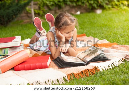 Little cute girl in dress lying on grass and looking at photos - stock photo