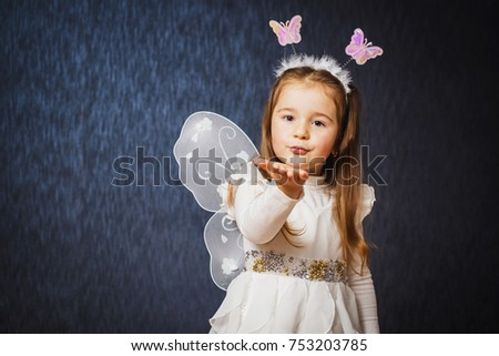 Little cute girl in fairy costume gives air kiss on dark blue background