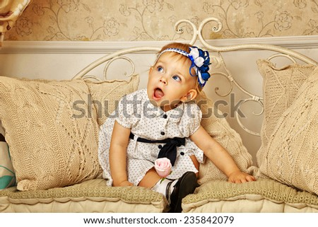 Little cute girl in French dress on a sofa with pillows