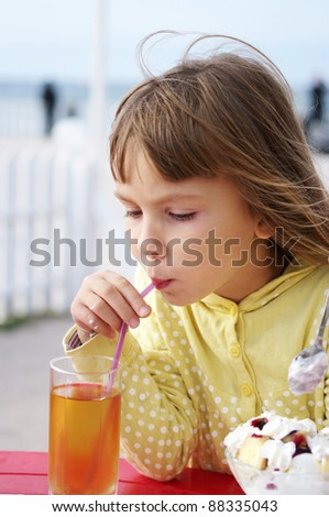Little cute girl in outdoor cafe.