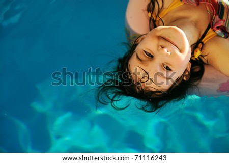 Little cute girl in pool with copy space - stock photo