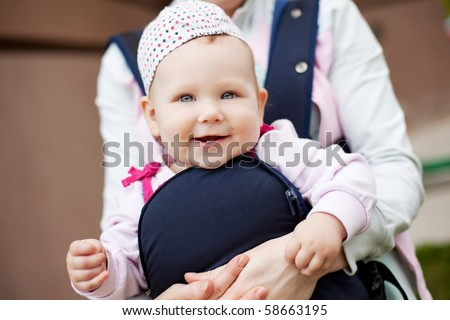 little cute girl in sling. Mother`s hand hold her. Summer time - stock photo