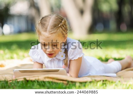 Little cute girl in summer park reading book