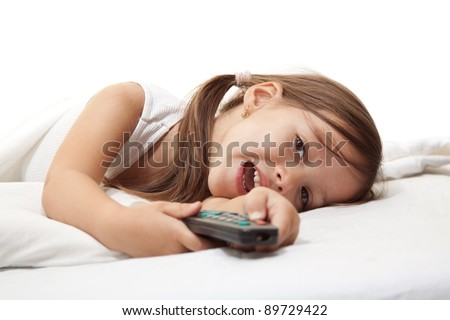 little cute girl in the bed, with a remote control in hand - stock photo