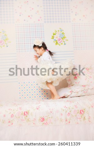 little cute girl in the cream lush dressy skirt is jumping on the bed - stock photo