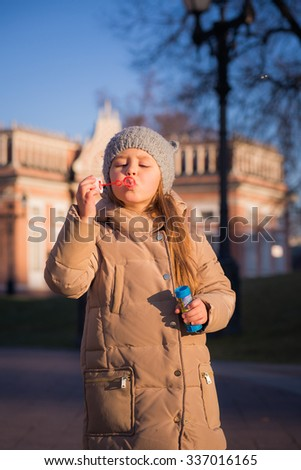 little cute girl in warm clothes walking and playing in the park in the late autumn. girl making soap bubbles and catches - stock photo