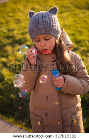 little cute girl in warm clothes walking and playing in the park in the late autumn. girl making soap bubbles and catches