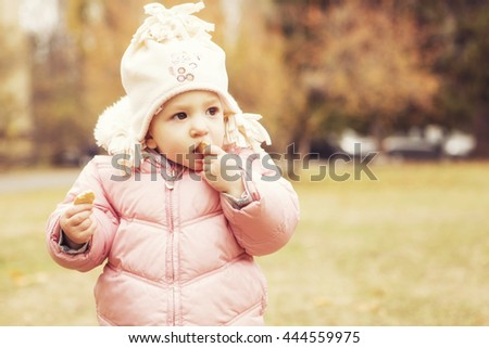 Little cute girl kid having fun in park in autumn warm clothes (pink jacket and a hat). Yellow fall leaves on a background. Lifestyle. Cold weather. Copy space