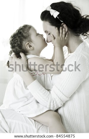 Little cute girl kissing her mother - stock photo