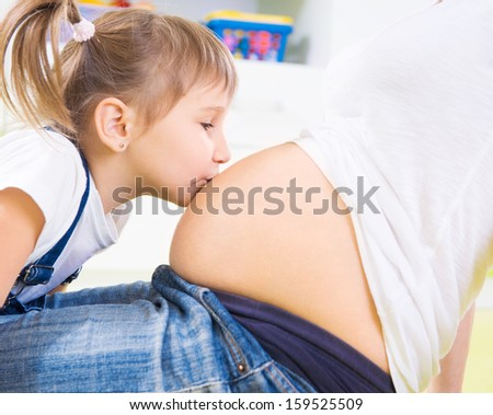 Little cute girl kissing pregnant mother's belly - stock photo