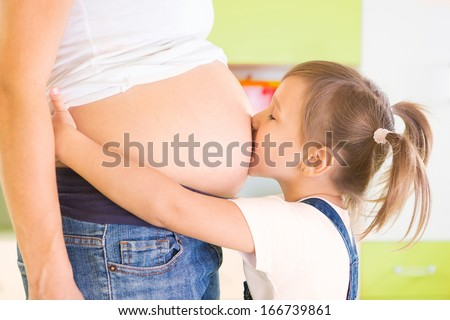 Little cute girl kissing pregnant mother's belly