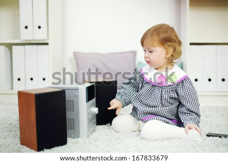 Little cute girl looks at music system on carpet in room at home. Shallow depth of field.