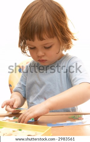 little cute girl making jigsaw puzzle isolated on white