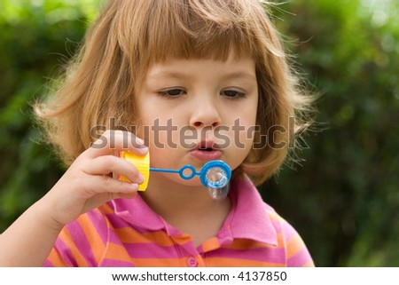 little, cute girl making soap bubbles outdoors