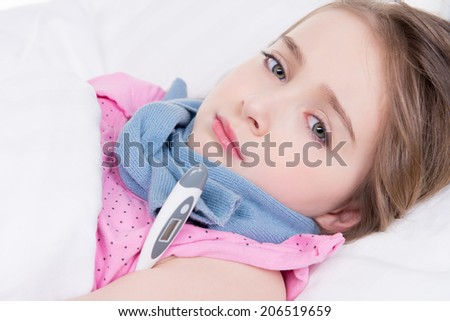 Little cute girl measures the temperature on a white background. - stock photo