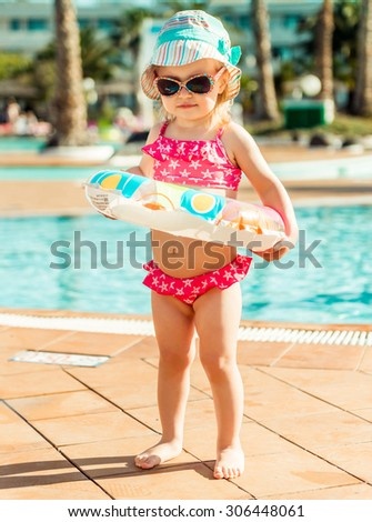 little cute girl near the pool with a circle for swimming - stock photo