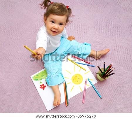 Little cute girl painting sun inside - stock photo