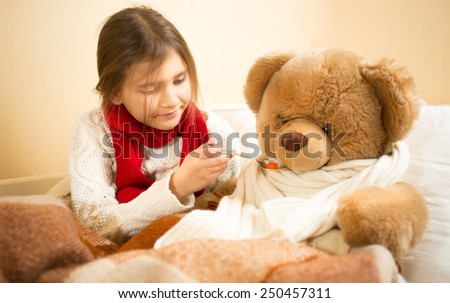 Little cute girl playing in hospital with teddy bear - stock photo